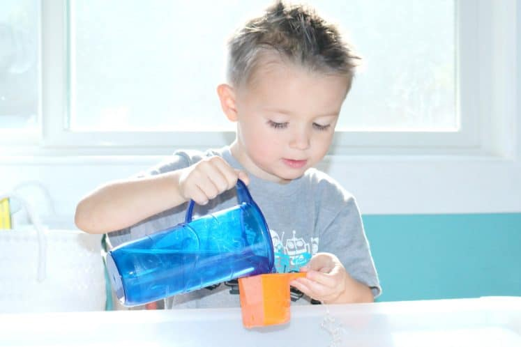 preschooler pouring water from small pitcher into measuring cup
