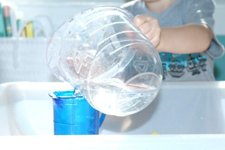preschooler pouring water into small pitcher