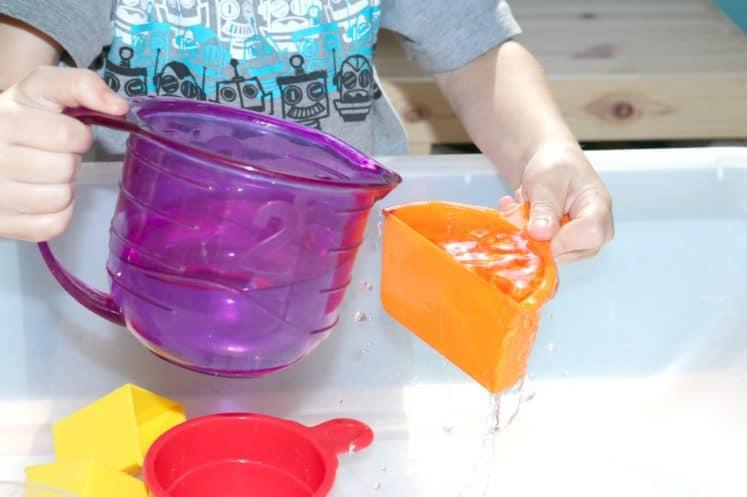 preschooler pouring water into measuring cup