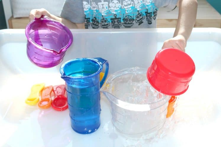 preschooler pouring water into clear container