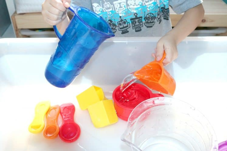 preschooler pouring water from one measuring cup to another