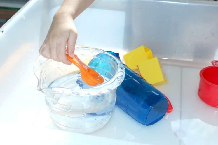 preschooler scooping water with measuring spoon