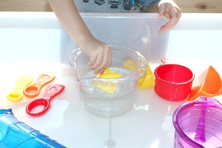 preschooler scooping water with measuring cup
