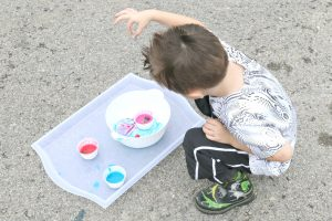 preschooler dropping rock into container for splatter painting activity