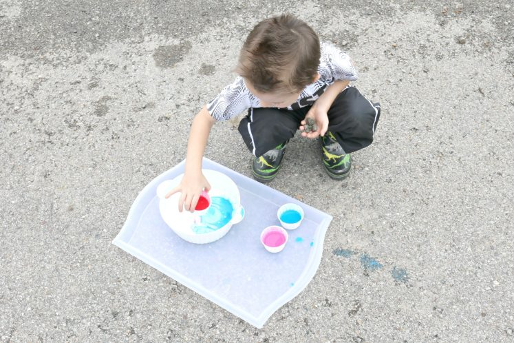 preschooler placing cup of paint into small bowl