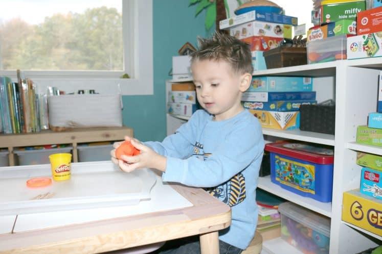 preschooler making a ball of playdough