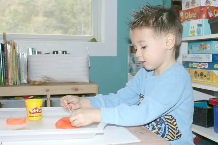 preschooler pushing toothpicks into playdough