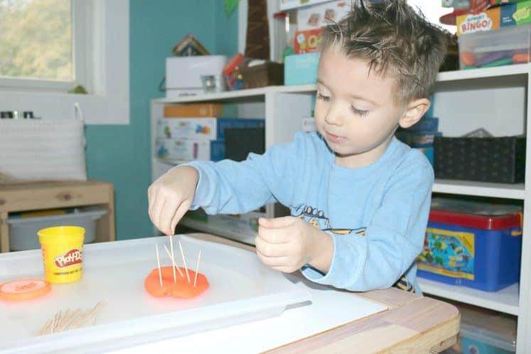preschooler pushing toothpicks into playdough to make porcupine quills