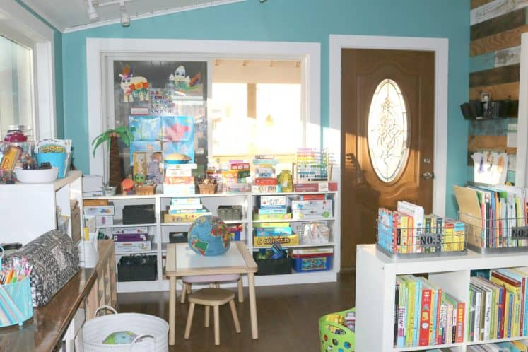 children's play area featuring shelves filled with toys, sensory table with stools