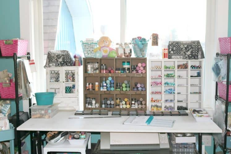 craft desk with wooden organizers containing paints, inks and markers