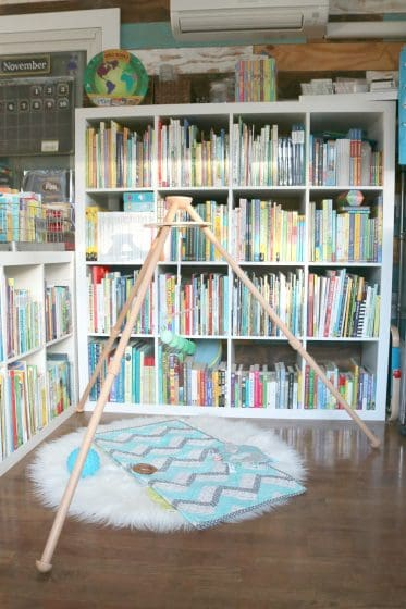 baby mobile with wooden stand in front of large cube bookshelves filled with children's books