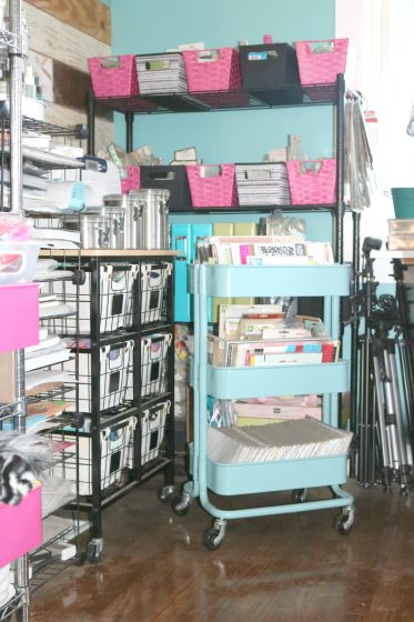 two different styles of rolling carts in front of wire shelf containing baskets filled with packaged embellishments