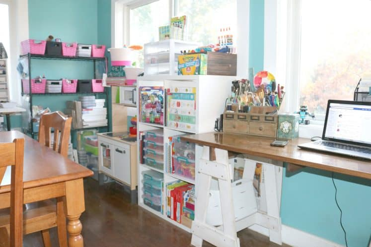 shared craft room with shelves full of supplies, pretend kitchen and desk workspace