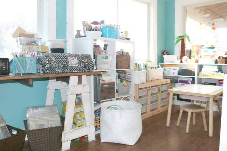 desk workspace next to children's play area featuring storage unit, sensory table with stools, and several bookshelves containing toys
