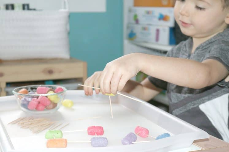 preschooler holding two toothpicks attached using a cornstarch noodle