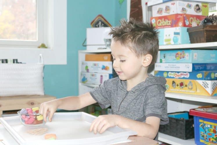 preschooler making bridges with cornstarch noodles and toothpicks