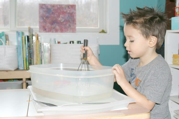 preschooler stirring moving water sensory bin