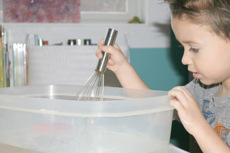 preschooler stirring water with metal whisk