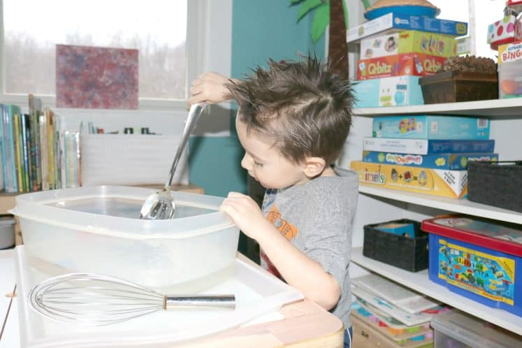preschooler stirring water for moving water sensory bin