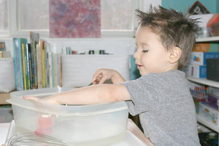 preschooler picking up object from moving water sensory bin