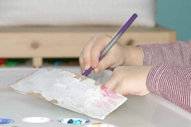 preschooler painting cardstock canoe