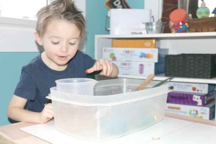 preschooler picking up plastic beaker from sensory bin