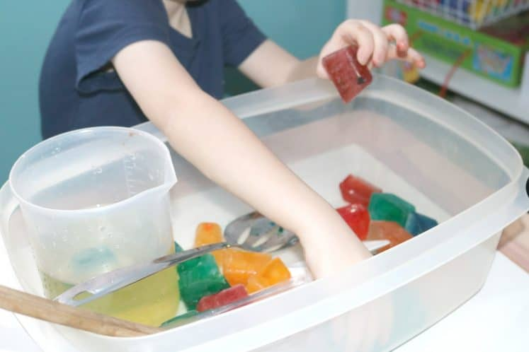 preschooler picking up colored ice cubes