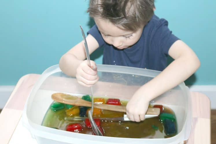 preschooler scooping colored ice from ice sounds sensory bin