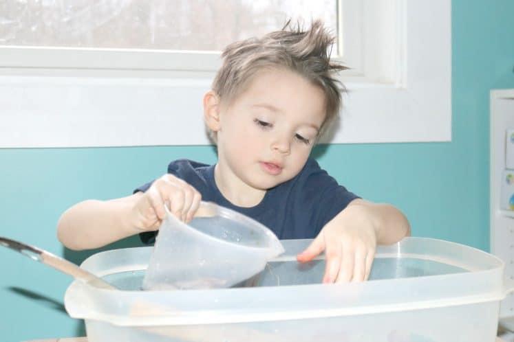 preschooler pouring water from beaker into sensory bin