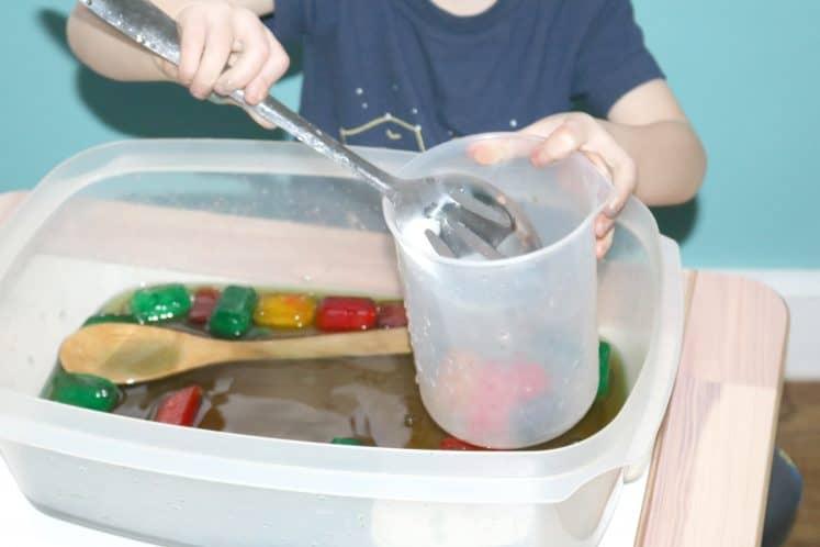 preschooler scooping colored ice into plastic beaker