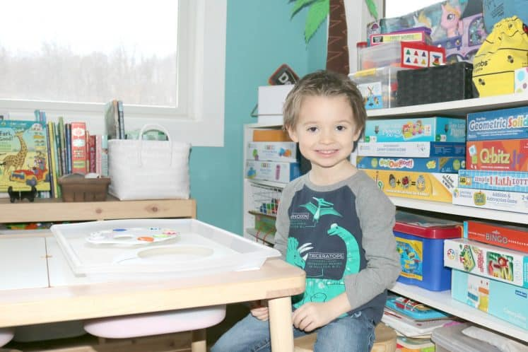 preschooler sitting at table ready to start paper plate necklace craft activity
