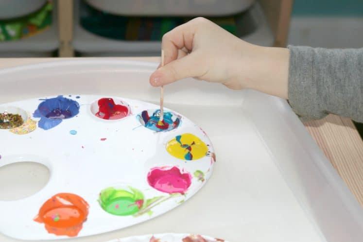 preschooler dipping cotton swab into paint palette