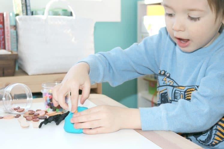 preschooler making beetle eyes using playdough