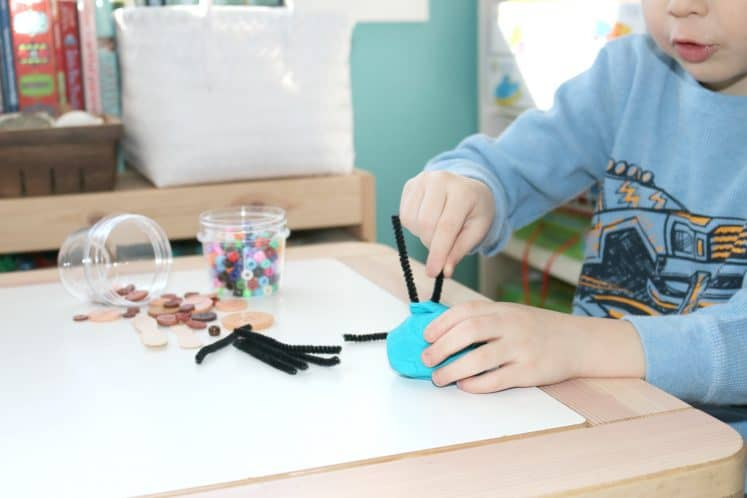 preschooler pushing pipe cleaners into playdough
