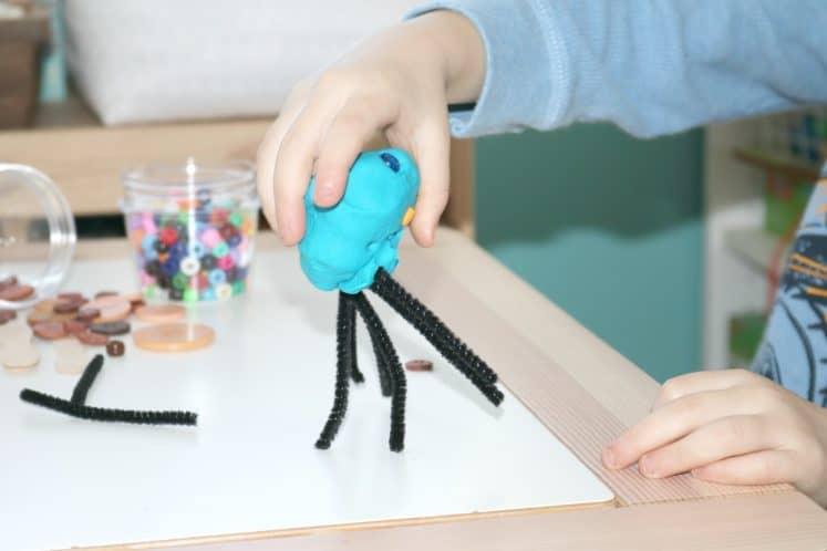 preschooler picking up beetle made from playdough