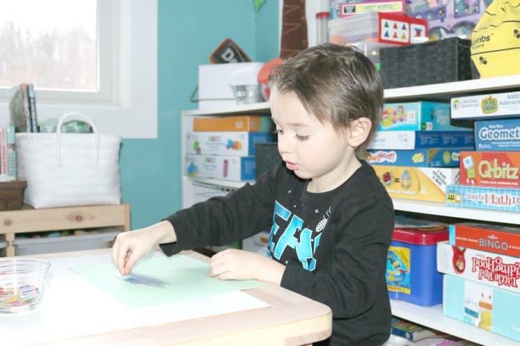 preschooler gluing mosaic squares to cardstock