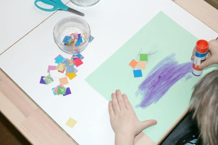 preschooler putting glue on cardstock to make migration art