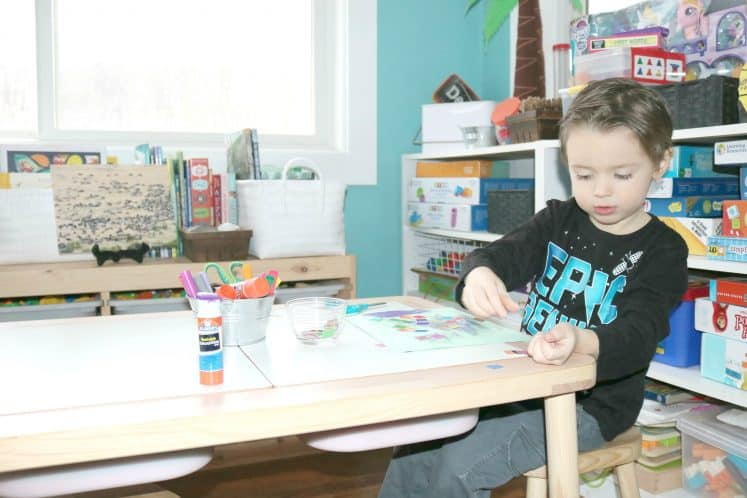 preschooler making migration process art by gluing mosaic squares to cardstock