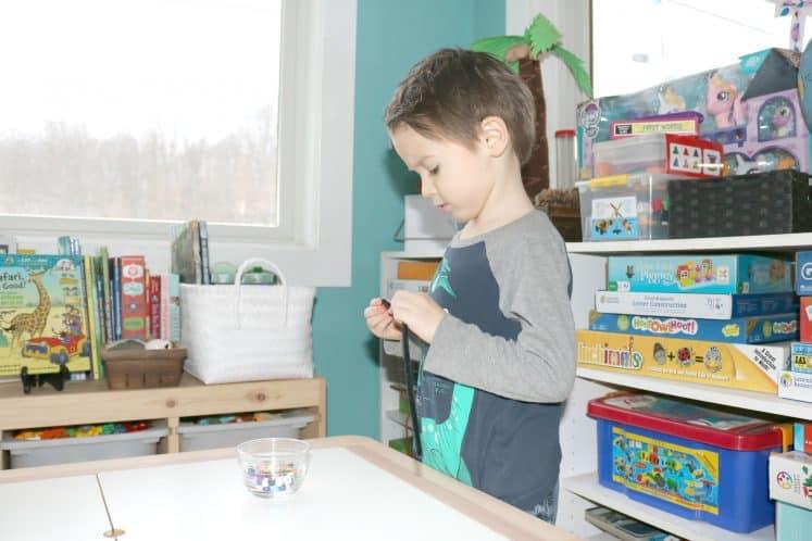 preschooler stringing beads on pipe cleaner