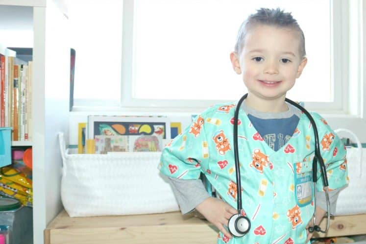 preschooler wearing scrub top and stethoscope standing with hands on hips smiling