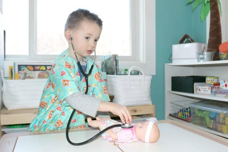 preschooler listening to baby doll's pretend heartbeat