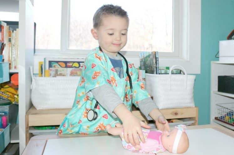 preschooler placing baby doll on pretend exam table