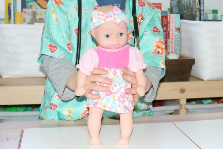 preschooler pretending to be a doctor and holding baby doll