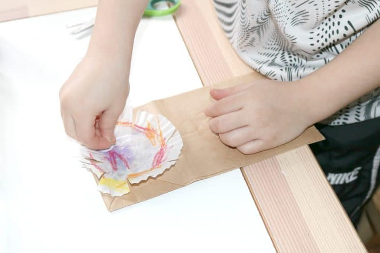 preschooler gluing wiggle eyes on paper bag lion craft