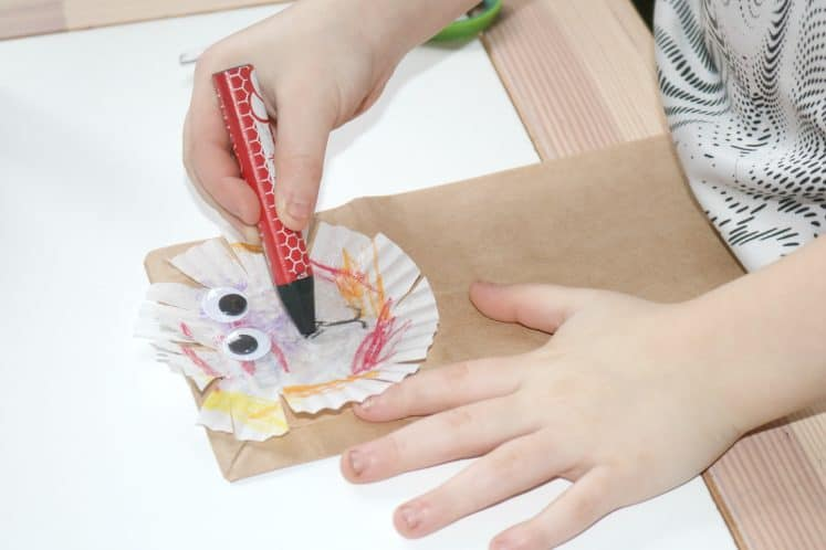 preschooler using crayon to add nose, mouth, and whiskers to paper bag lion craft