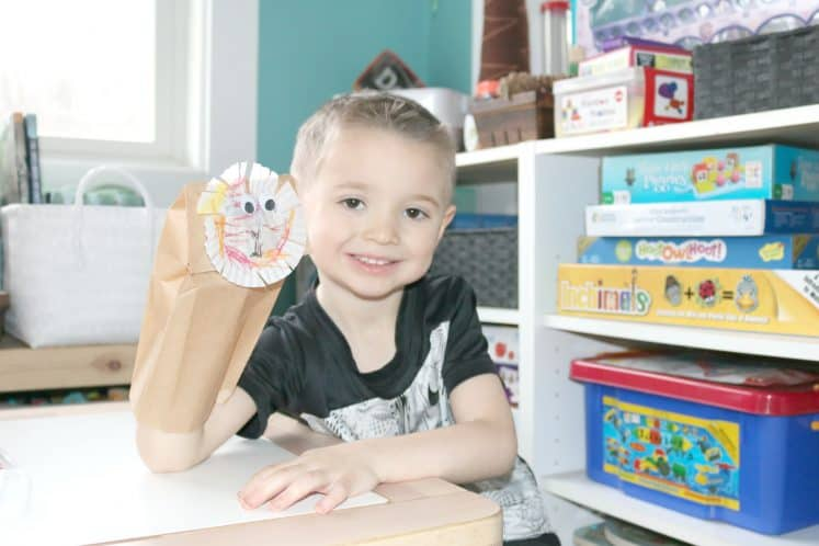 preschooler holding paper bag lion puppet and smiling