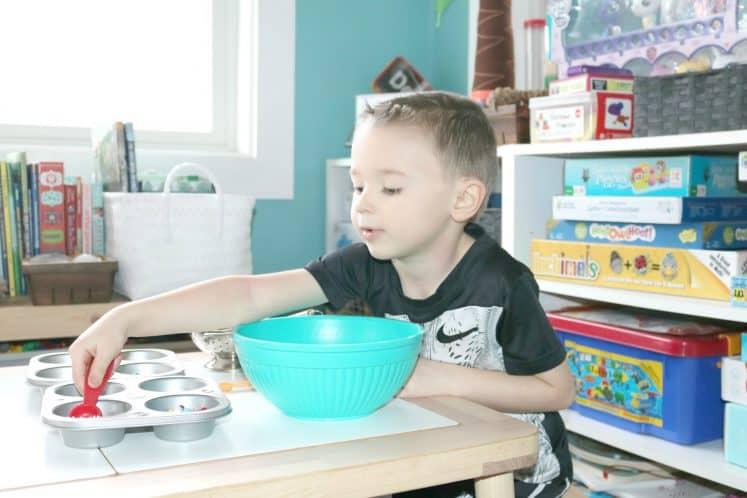 preschooler scooping loose parts with measuring spoon