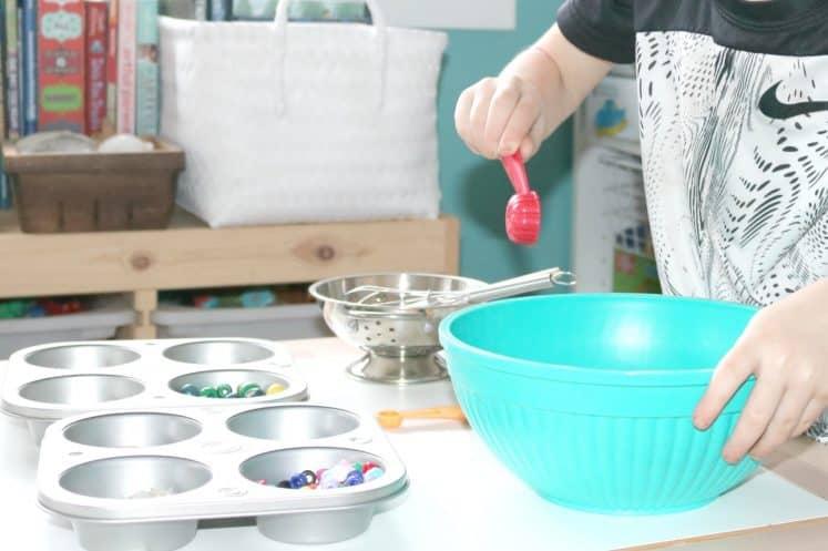 preschooler exploring kitchen-themed loose parts activity