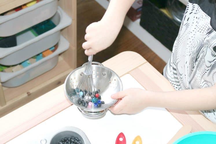 preschooler stirring beads in colander with whisk