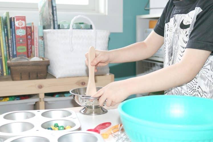 preschooler using wooden spoon to stir loose parts in metal colander